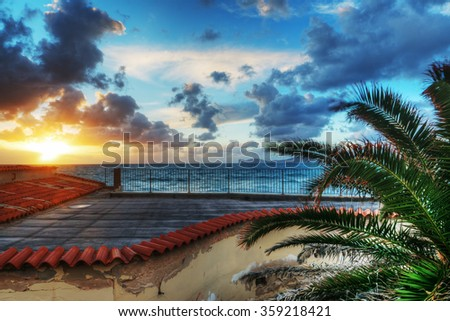 palm and terrace by the sea at sunset, Italy