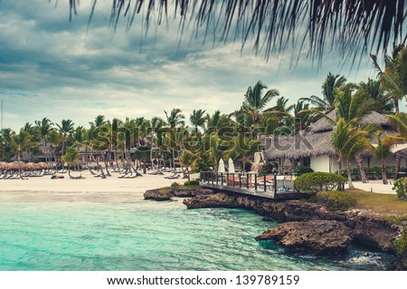Palm and tropical beach in Tropical Paradise. Summertime holyday in Dominican Republic, Seychelles, Caribbean, Philippines, Bahamas. Relaxing on remote Paradise beach. Luxury Resort on Atlantic ocean. - stock photo