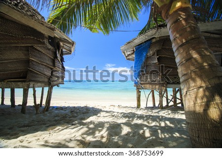 palm bungalows on  white sand beach with palm tree and view on azure sea  in polynesia - stock photo