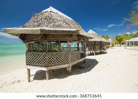 palm bungalows on  white sand beach with view on azure sea  in polynesia - stock photo