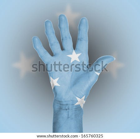 Palm of a woman hand, painted with flag of Micronesia