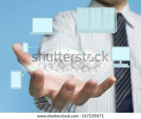 Palm opening businessman with cloud gear inside and electric devices and blue sky background, cloud computing service concept - stock photo