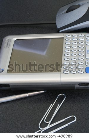 Palm Pilot, paper clips, stylus, mouse, pen - stock photo