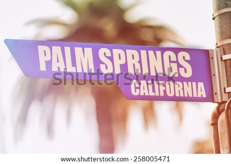 Palm Springs California Street Sign. A street sign marking Palm Springs, California. Backed by a palm tree with a sunset flare. - stock photo