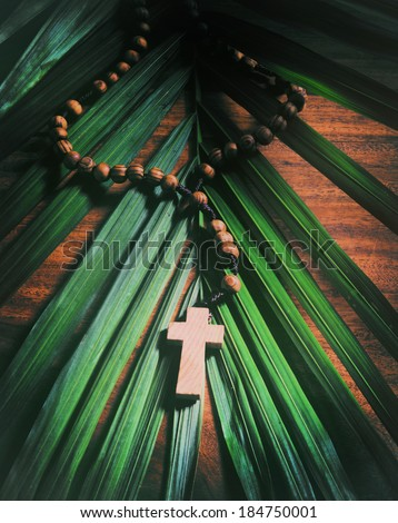 Palm Sunday still life - A beaded olive wood cross or rosary rests upon a palm branch on top of a rustic table.  Processed for an aged vintage look.     - stock photo
