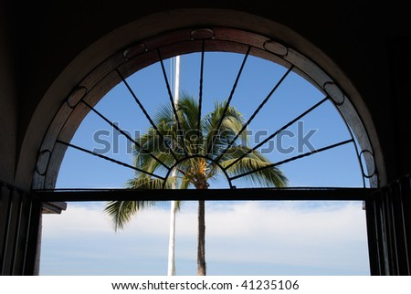 Palm Tree and Arch Window from a restaurant on the Malecon in old town Puerto Vallarta, Mexico, - stock photo