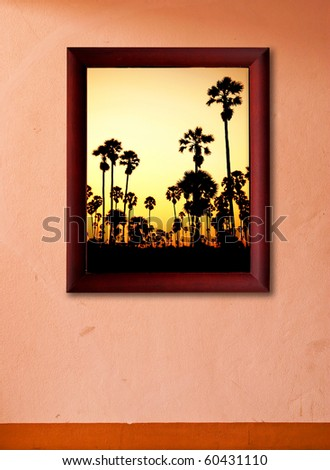 palm tree in wooden frame on pink wall - stock photo
