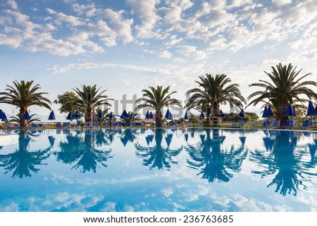 Palm trees, beach sunbeds and umbrellas near the pool by the sea. Beautiful reflection. - stock photo