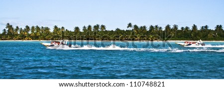 Palm trees, blue sky, ocean water and two speedboats racing past a sandy tropical beach