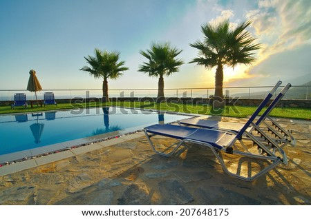 Palm trees, lounge chairs, and pool on a summer vacation - Sunrise and mist over the Cretan mountains with picture-perfect palm trees reflecting in a pool in Malia, Crete near Heraklion (HDR image) - stock photo