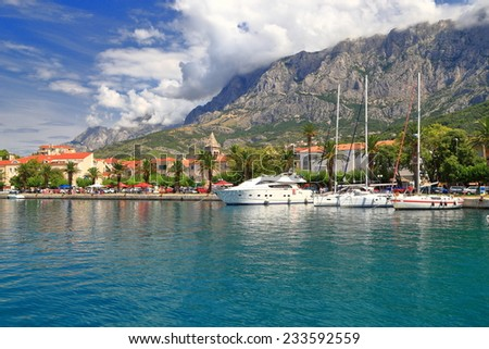 Palm trees on a pier of Venetian town with sail boats at anchor, Makarska, Croatia - stock photo