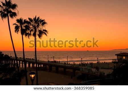 Palm trees on the Manhattan Beach, Pier and beach clock tower, Los Angeles, California - stock photo