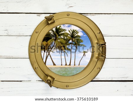 Palm trees on tropical island seen through vintage brass porthole in wooden wall - stock photo