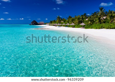 Palm trees over stunning lagoon and white sandy beach - stock photo