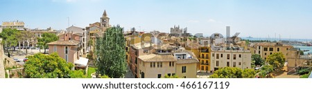 Palma de Majorca, Spain - June 25, 2008: View over Port de Palma from museum Es Baluard - palm and old wall in front