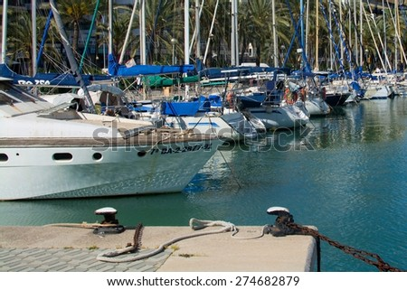 PALMA DE MALLORCA, SPAIN - APRIL 19, 2015: Mediterranean maritime scene with yachts, palm trees and moorings on April 19, 2015 in Palma de Mallorca, Balearic islands, Spain.