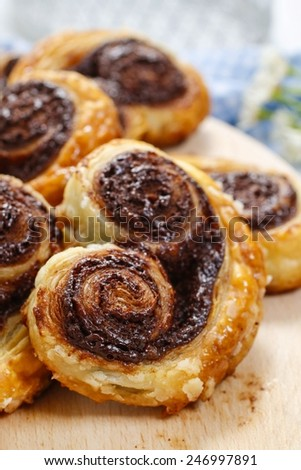 Palmier biscuits - french cookies made of puff pastry and chocolate (also called palm leaves, elephant ears, french hearts, shoe-soles or glasses) - stock photo