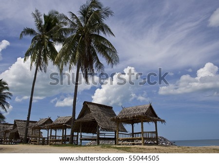 palms and bungalows next to water - stock photo