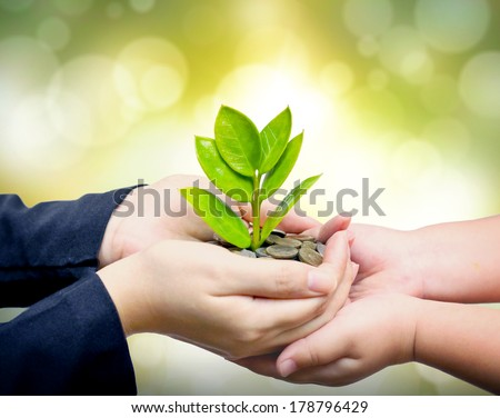 Palms with a tree growing from pile of coins supported by kid's hands /  hands giving a tree growing on coins to child's hands / csr green business / business ethics - stock photo