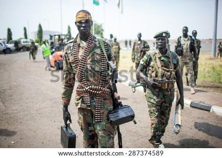 Paloch, South Sudan - March 2, 2014: A South Sudanese soldier carries a machine gun - stock photo