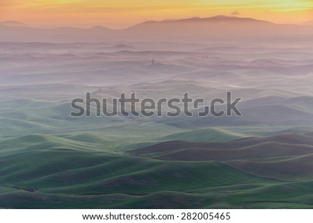 Palouse rolling hills in sunrise, the view from Stepteo Butte State Park. The low light and low rolling hills in different colors and shade are unique beauty of this Eastern Washington area. - stock photo