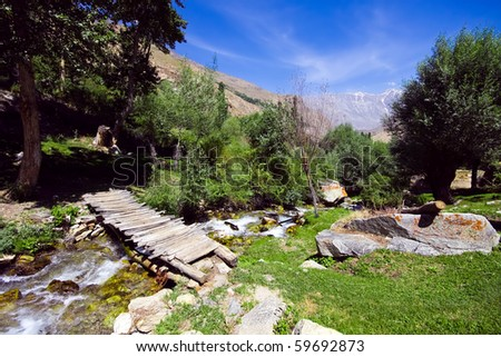 Pamir mountain bridge over spring and green lonely landscape under blue sky in the springtime - stock photo