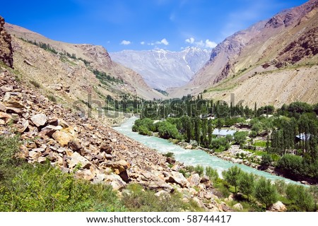 Pamir mountain morraine river and green lonely village under blue sky - stock photo