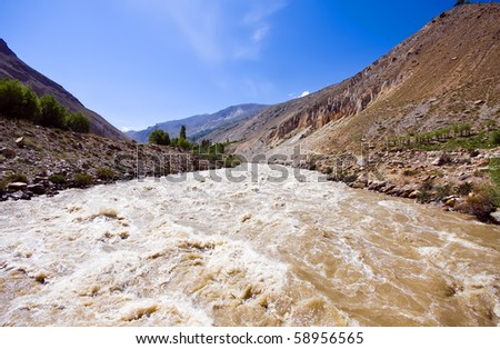 Pamir mountain muddy river under blue sky during summertime - stock photo