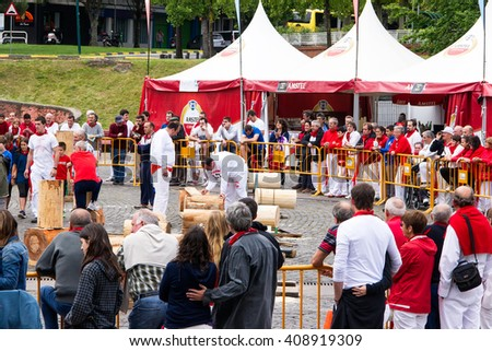 PAMPLONA, SPAIN - JULI, 09,2014: The people in festive clothes during San Fermin look at the competitions wood chopping, a traditional Basque custom. - stock photo