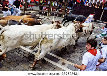 PAMPLONA, SPAIN - JULY 8, 2015: Bulls and people are running in street during San Fermin festival. Festival has been held annually for several centuries