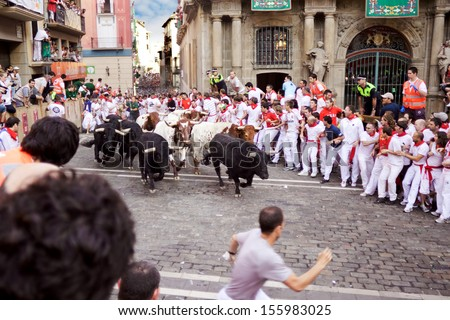 PAMPLONA, SPAIN-JULY 9: Bulls and people are running in street during San Fermin festival in Pamplona, Spain on July 9, 2013. - stock photo