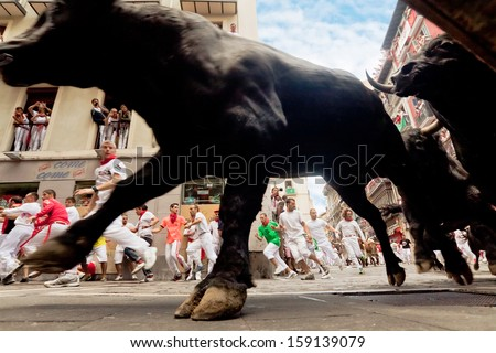 PAMPLONA, SPAIN-JULY 13: Bulls and people are running in street during San Fermin festival in Pamplona, Spain on July 13, 2013. - stock photo