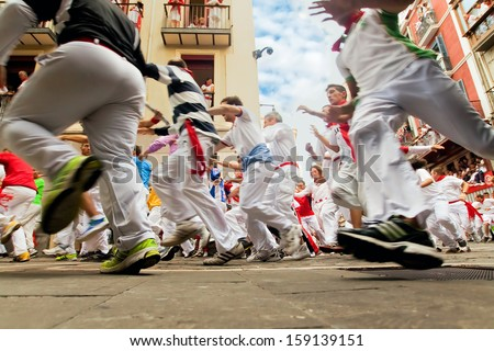 PAMPLONA, SPAIN-JULY 12: People run from bulls on street during San Fermin festival in Pamplona, Spain on July 12, 2013 - stock photo