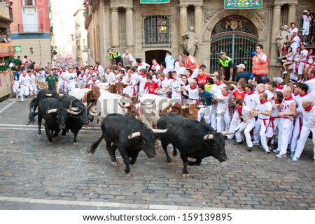 PAMPLONA, SPAIN-JULY 9: People run from bulls on street during San Fermin festival in Pamplona, Spain on July 9, 2013.. - stock photo