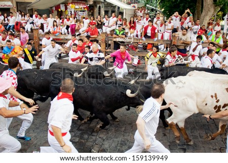 PAMPLONA, SPAIN-JULY 10: People run from bulls on street during San Fermin festival in Pamplona, Spain on July 10, 2013 - stock photo