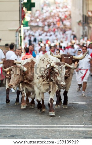 PAMPLONA, SPAIN-JULY 9: People run from the bulls on the street during San Fermin festival in Pamplona, Spain on July 9, 2013.. - stock photo