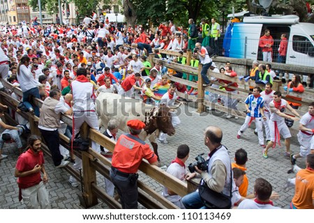 PAMPLONA, SPAIN -JULY 8: Unidentified men run from the bulls in front plaza Toros during the San Fermin festival in Pamplona, Spain on July 8, 2012. - stock photo