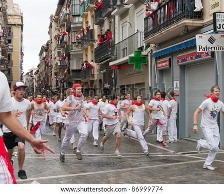 PAMPLONA, SPAIN -JULY 7: Unidentified men run from the bulls in the street Estafeta during the San Fermin festival in Pamplona, Spain on July 7, 2011. - stock photo