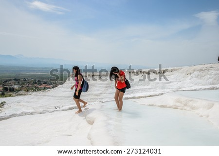 PAMUKKALE, TURKEY - APR 18, 2015: Unidentified girls walk over the travertines of Pamukkale, Turkey. It's a UNESCO World Heritage site