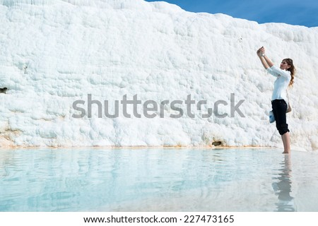 PAMUKKALE, TURKEY - OCTOBER 17, 2014: A woman is making a selfie using her mobile phone standing in a travertine pool which is part of the natural phenomenon around the pools of Pamukkale on October - stock photo