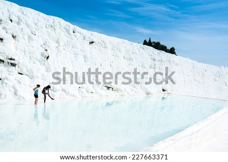 PAMUKKALE, TURKEY - OCTOBER 17, 2014: Two young women are applying white mud containing chalk while standing in a travertine pool which is part of the natural phenomenon around the pools of Pamukkale - stock photo