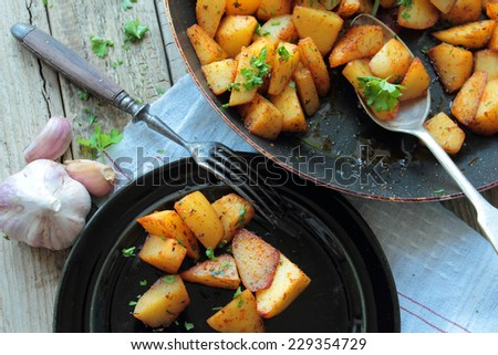 Pan and plate with fried potatoes with herbs - stock photo