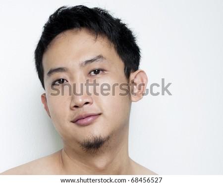 Pan Asian male portrait on plain background - stock photo