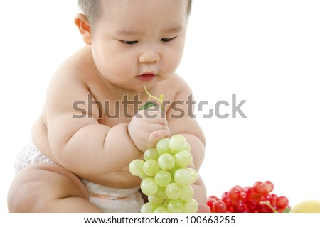 Pan Asian Vegetarian baby playing with fruits on white background