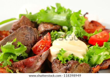 Pan fried chicken livers with salad greens and bacon strips