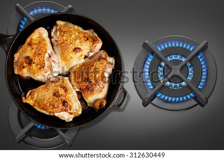 Pan fried chicken on the gas stove top view - stock photo