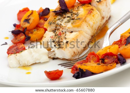 Pan fried halibut garnished with fennel seeds and spicy mustard sauce, served with fried cherry tomatoes salad with purple basil - stock photo