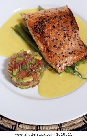 pan fried or sauteed salmon fillet on asparagus and lemon butter sauce, served with avocado, tomato and onion salsa. Flesh side up showing rich red 'grill' effect and pepper. - stock photo