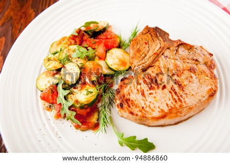 Pan Fried Pork Chop with Bone Served with Sauteed Tomatoes, Zucchini, Fresh Arugula