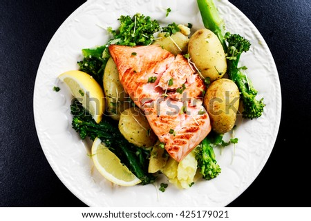 Pan fried Salmon Served with potatoes and tenderstem broccoli. - stock photo